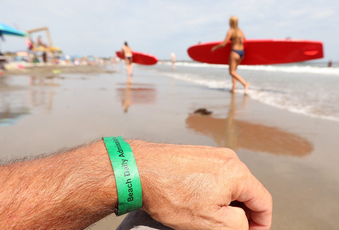 People who don't have season passes to Narragansett Town Beach have to pay a $12 daily admission fee to get a wristband.