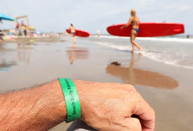 People who don't have season passes to Narragansett Town Beach have to pay a daily admission fee to get a wristband for entry.