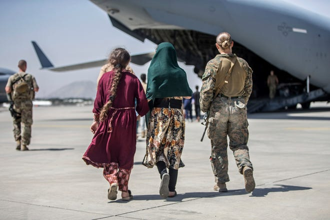 A U.S. Marine walks with a family during evacuations in Kabul, Afghanistan last week. About 30 members of the Rhode Island Air National Guard will help provide housing and other assistance to Afghan refugees at a military installation in New Jersey.