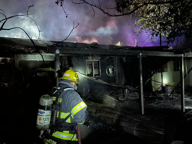 A firefighter responds to a house fire in north Springfield Monday night. The home was likely totaled, according to fire officials.