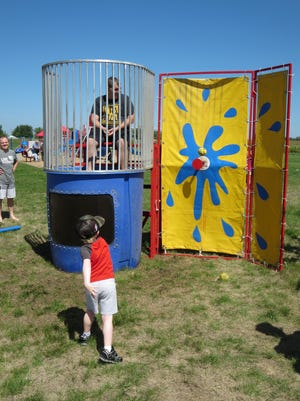 Rodney Vermillion takes a shot at dunking 7th and 8th grade teacher Mr. Westenberg during the St. John Lutheran School Hog Roast, an annual back to school community event, held on Sunday, Aug. 29. Families enjoyed a meal—roasted hog, potato salad, beans, chips, fruit and a desert bar—along with the fun of bouncy houses, cotton candy, snocones, face painting, and music.