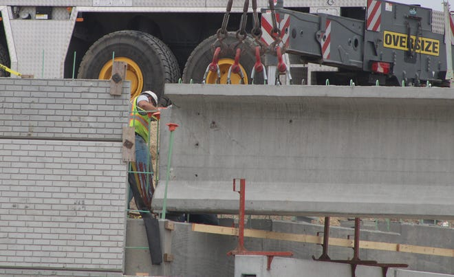 A worker helps place beams along the future Ohio Street overpass in Martinsville.