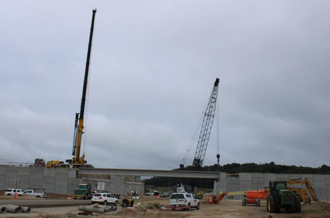 Two cranes set bridge beams for the future Ohio Street overpass that will carry traffic over I-69 in Martinsville.