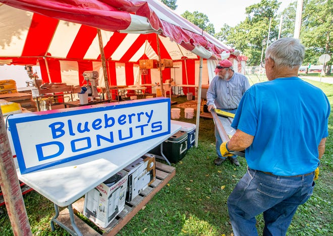 Jon Pairitz, left, and Richard Parker work together at the Blueberry Donuts tent as setup continues for the Marshall County Blueberry Festival on Tuesday at Centennial Park in Plymouth.