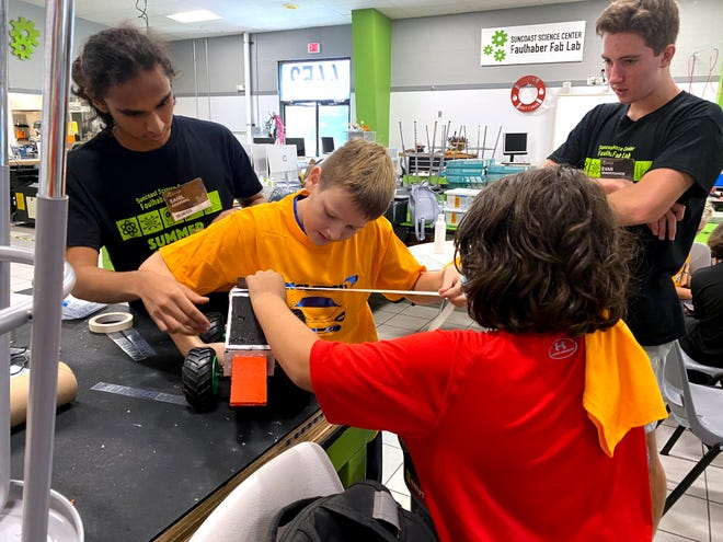 Fab Lab volunteers Sahil and Evan help their engineering students with a project. STEAM Saturdays are returning on Oct. 2 with a wide range of courses.