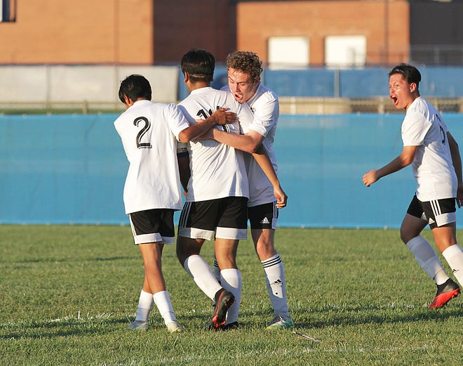 Sturgis' Brandin Kelley shares a hug with Esteban Lopez (14) and Steve Gonzalez (2) after Lopez booted in a penalty kick to give Sturgis a 3-2 advantage late in the game.