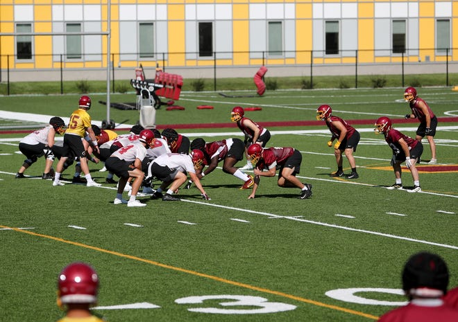 Northern State football players watch during a practice as quarterback Michael Bonds (15) takes a snap in a drill. American News photo by Jenna Ortiz, taken 08/10/2021.