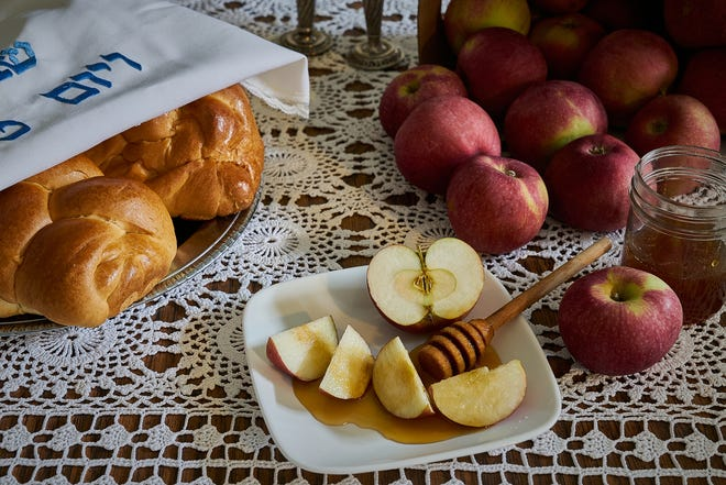 A Rosh Hashana holiday table with apples, honey and challah.