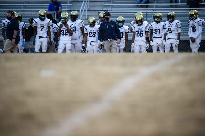 E.E. Smith players stand on the sideline during a game during the spring 2020-21 football season.