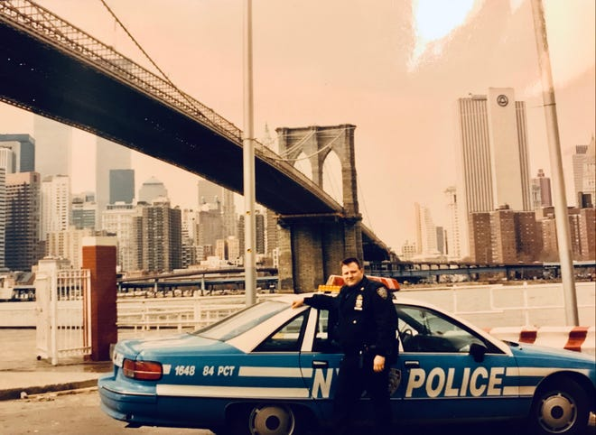 Bob Young worked as an officer for the New York City Police Department from 1991 until 2008. This photo, taken in 1991, shows him standing in front of the Brooklyn Bridge. The World Trade Center towers can be seen in the background.