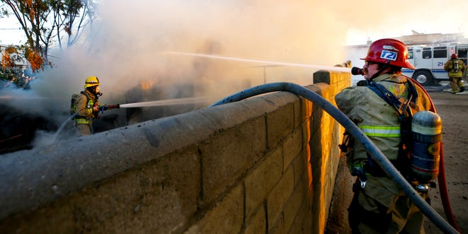 Firefighters at scene of fire  in outbuilding on 300 block of Kern Street Monday evening.