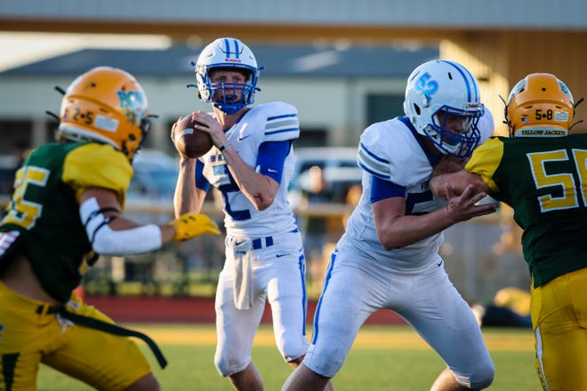 VAHS quarterback Gavin Montgomery drops back to pass with protection from lineman Zach Thomas.