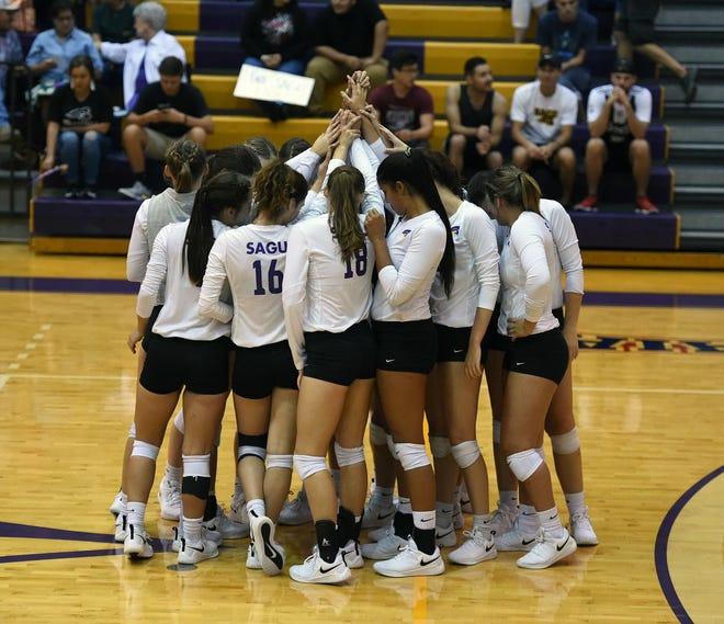 The SAGU volleyball team huddles during a recent match.