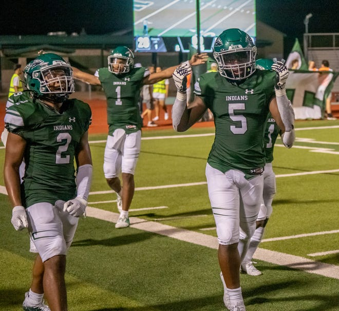 Waxahachie football players Iverson Young (2), Jayden Becks (5) and Roderick Hartsfield Jr. (1) celebrate as they walk off the field following the Indians' 28-22 overtime victory over Rowlett at Lumpkins Stadium on Friday night.