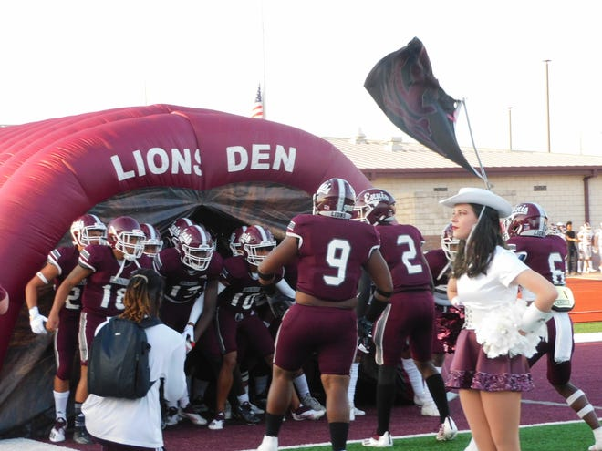 Ennis football players get ready to take the field for the start of Friday night's game against Red Oak at Lions Memorial Stadium. The Lions defeated the Hawks, 56-42.