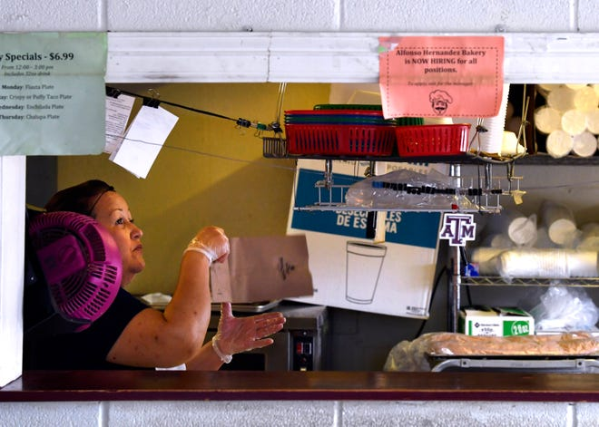Mirna Guardado makes burritos at Alfonso Hernandez Bakery in Abilene August 6, 2021. In the serving window, a Help Wanted sign hangs, a common sight at restaurants around the region since the pandemic.