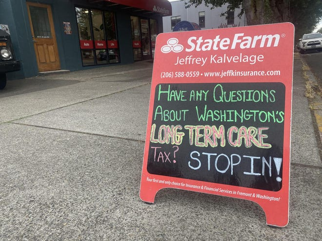 A sandwich board sits outside an insurance broker's office in Seattle's Fremont neighborhood on Aug. 26, inviting passersby to come in and ask questions about Washington's long-term care tax.