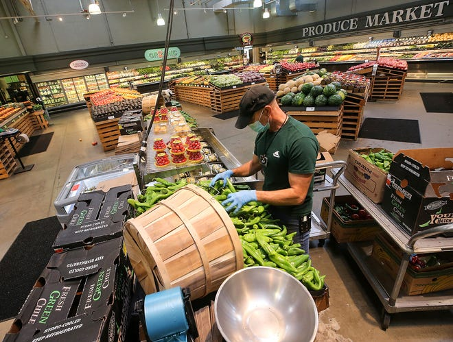 Rob Ramsey arranges a display of hatch chile peppers as he and fellow produce clerks restock the produce section at Central Market in Poulsbo on Tuesday.