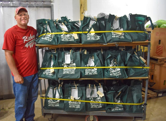Phil Riehm stands next a few of the packed CSA bags inside a cooler at Riehm Produce Farm. The farm distributes about 700 CSA bags weekly.