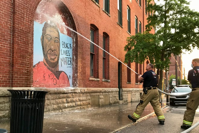 Lafayette firefighters use a hose to remove white paint that was thrown at the George Floyd mural painted in the summer of 2020 at 6th and Ferry Streets, Monday, Aug. 30, 2021 in Lafayette.