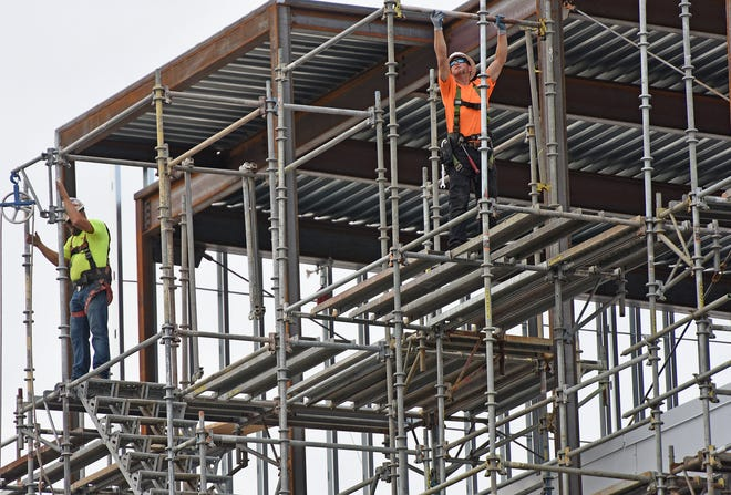 Workers assemble scaffolding outside theAvita Health System Ontario Hospital at the Richland Mall on Tuesday.
