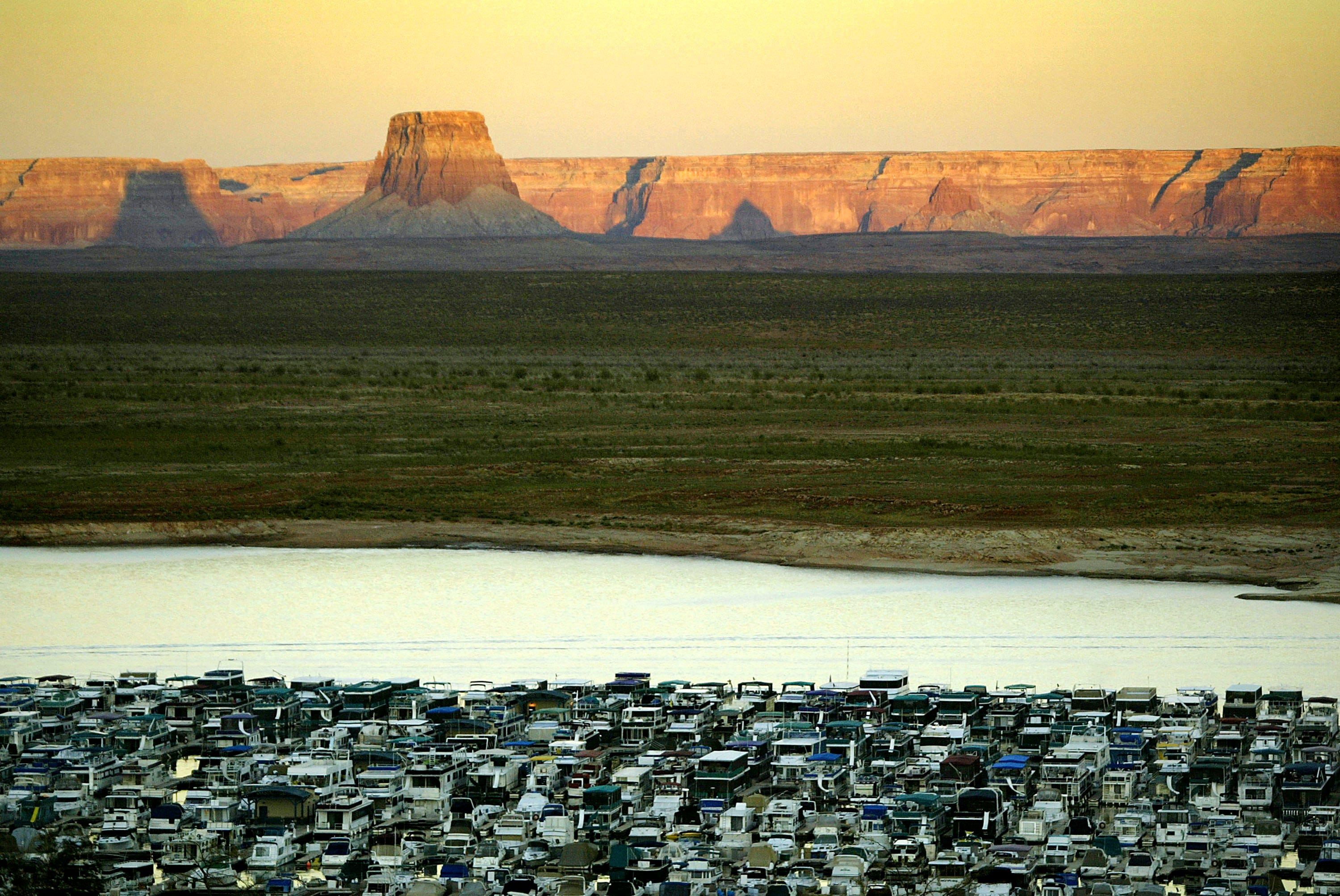 PAGE, AZ - SEPTEMBER 25: Hundreds of boats are docked at Wahweap on Lake Powell as the five-year-old Western drought continues on September 25, 2004 near Page, Arizona. The seven states sharing the Colorado River are considering a plan to protect Lake Powell by cutting the amount of water released downstream to Lake Mead, the primary water supply for Las Vegas. The drought has left the two massive reservoirs that catch the Colorado River less than half full, exposing long-submerged landscapes to direct sunlight for the first time in decades and officials fear that the levels will fall too low to turn the electric turbines that produce electricity. The river provides water for 25 million people, millions of acres of farmland, and an assortment of endangered and other animals. It could reportedly take a 10-year run of average rain and snow to refill the reservoirs.           (Photo by David McNew/Getty Images) ORG XMIT: 51332881
