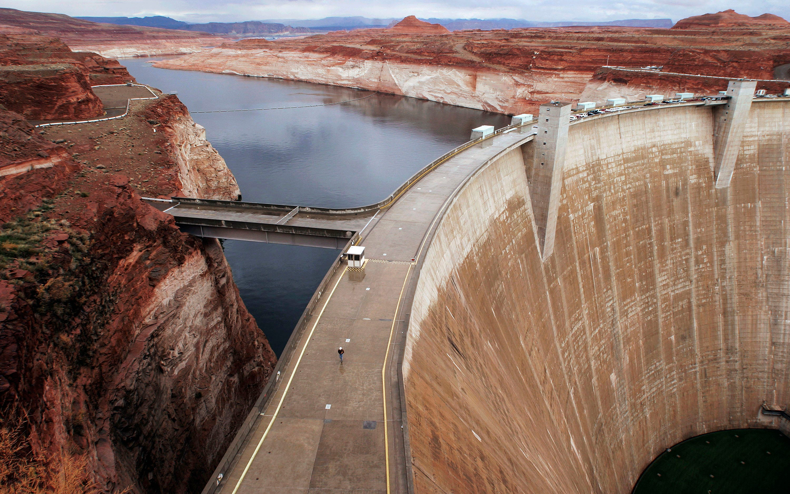 PAGE, AZ - NOVEMBER 22:  An employee walks across Glen Canyon Dam with Lake Powell in the background November 22, 2004 in Page, Arizona. Completed in 1963 the dam, at full pool, holds 26 million acre feet of water. A six year drought has reduced that amount to nine million acre feet today and lowering the level of the lake by 130 feet. The Bureau of Reclamation is releasing water from the dam in a five day simulated flood ending November 25. The flood will move sediment down the Colorado River building up beaches and improving natural habitat through the Grand Canyon.  (Photo by Jeff Topping/Getty Images)