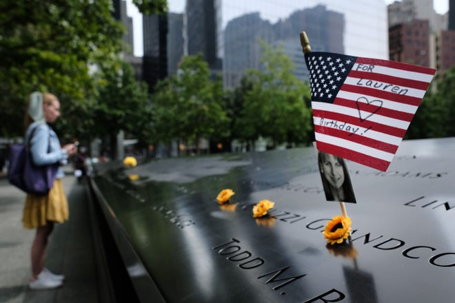 A U.S. flag is placed near a victim's name at the Sept. 11 Memorial at Ground Zero on Aug. 31, 2021 in New York City. New York City and much of the nation are preparing for the 20th anniversary of the terrorist attacks in both New York City and Washington, D.C.