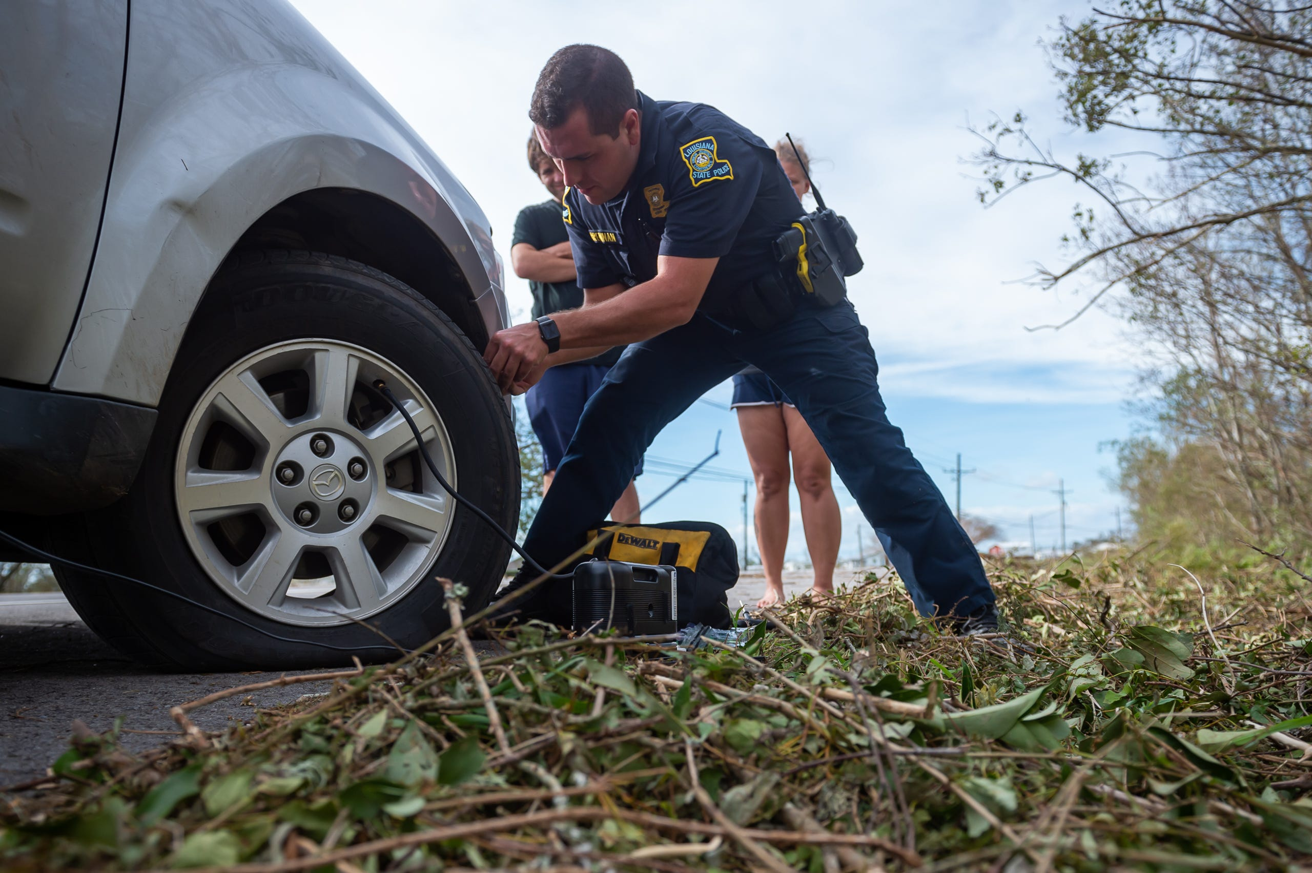 Louisiana State Trooper Ross Brennan assist motorist Justin Emmendorfer and Alexis Perry with changing and repaiiring a flat tire. Monday, Aug. 30, 2021.