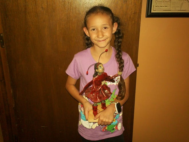 Isabella Jimenez displays her pried sculpture created by local artist Diana Le Marbe.