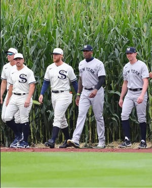 Members of the White Sox and Yankees, including Palm Desert grad Brooks Kriske (right) emerge from the corn before the Field of Dreams game in Iowa on Aug. 12