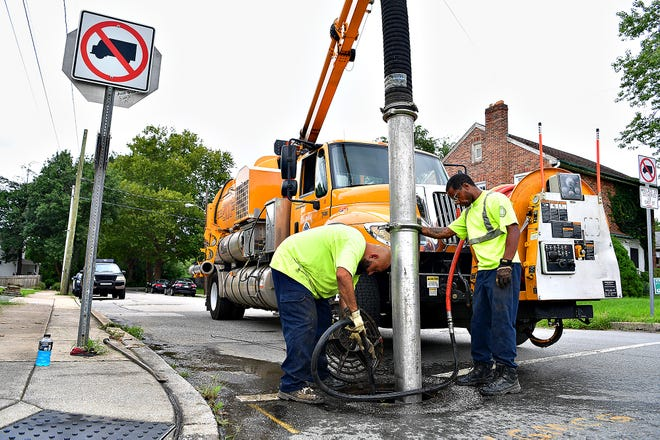 York City operators Hectar Vargas, left, and Tavares Outen spray water into the storm drain to help loosen debris for removal at the intersection of South Harrison and East Philadelphia streets in York City, Tuesday, Aug. 31, 2021. The stop was their last of seven to check and clear drains prone to flooding throughout the city in anticipation of heavy rain Wednesday. Dawn J. Sagert photo