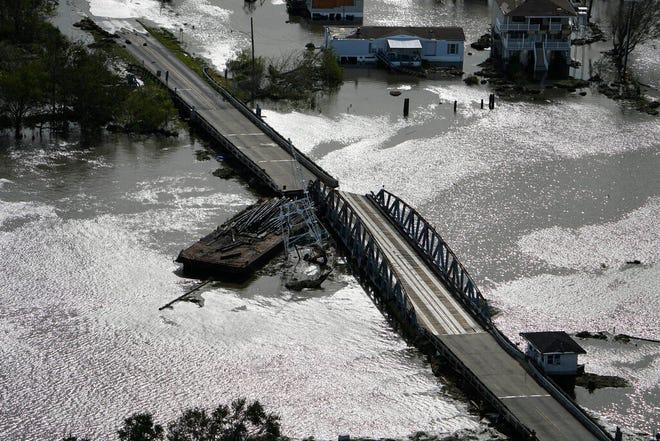A barge damages a bridge that divides Lafitte, La., and Jean Lafitte, in the aftermath of Hurricane Ida, Monday, Aug. 30, 2021, in La. (AP Photo/David J. Phillip)