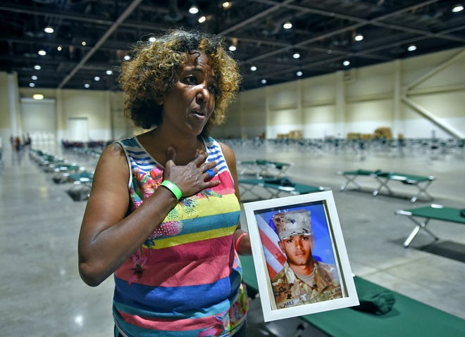 Standing in the evacuation center at the Reno-Sparks Convention Center on August 31, 2021, Evacuee Yasmin Mesfin holds a picture of her son that she bought with when she evacuated her South Lake Tahoe home. She hasn't seen her son for 7 years.