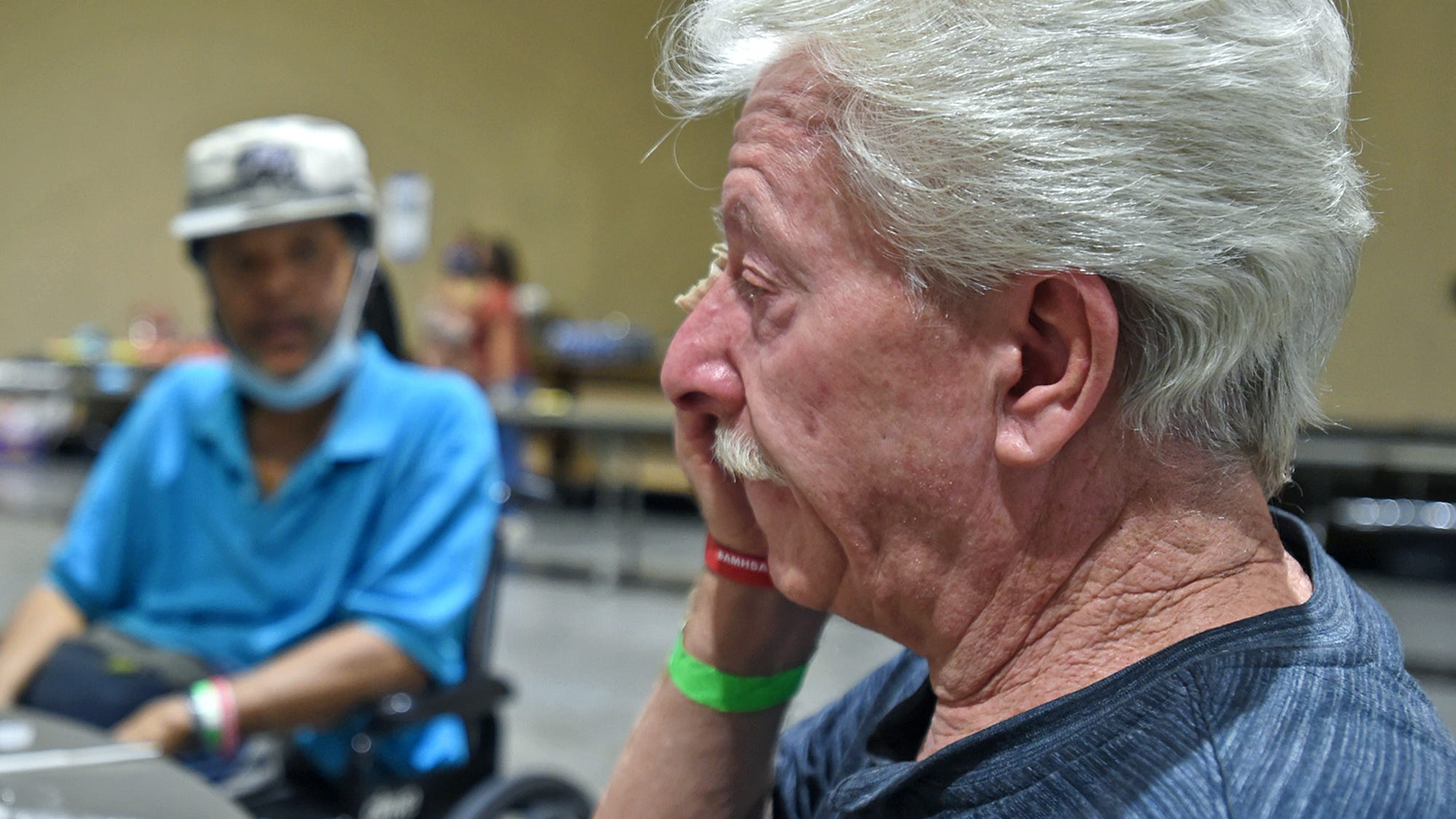 Having lunch at the evacuation center at the Reno-Sparks Convention Center, Timothy Pritchard wipes a tear away as he talks about what he left behind at his South Lake Tahoe home. Next to him is newfound friend Paul Brooks who had to call 911 to help him get out because he's in a wheelchair.