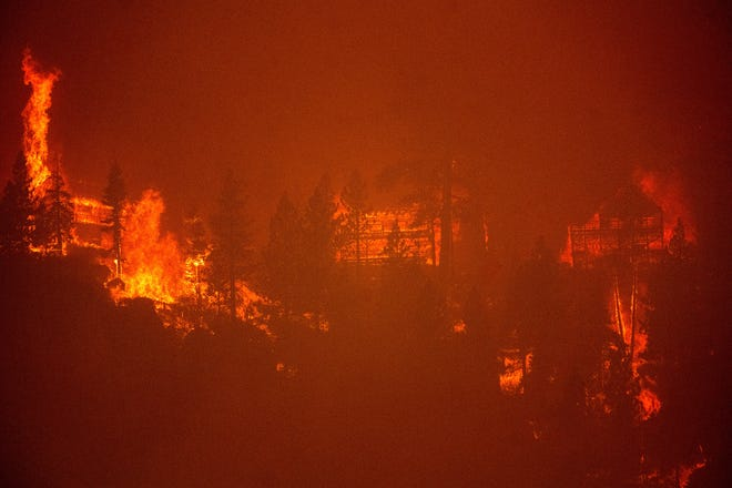 Seen from South Lake Tahoe, Calif., flames from the Caldor Fire consume three homes on Monday, Aug. 30, 2021. (AP Photo/Noah Berger)