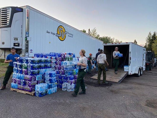 """This photo provided by the U.S. Forest Service-Superior National Forest in Minnesota shows people unloading donated supplies in Finland, Minn. Officials leading the fight against wildfires in northern Minnesota warned Monday, Aug. 30, 2021, about a new threat: bears attracted by generous donations of food and other supplies."""" Donations have far out-stripped our need and our ability to store what we have received,"""" Superior National Forest officials posted in a social media update. """"We have no remaining storage space and donations now must be stored in the open on pallets, making them an attractant to bears. (U.S. Forest Service-Superior National Forest via AP)"""