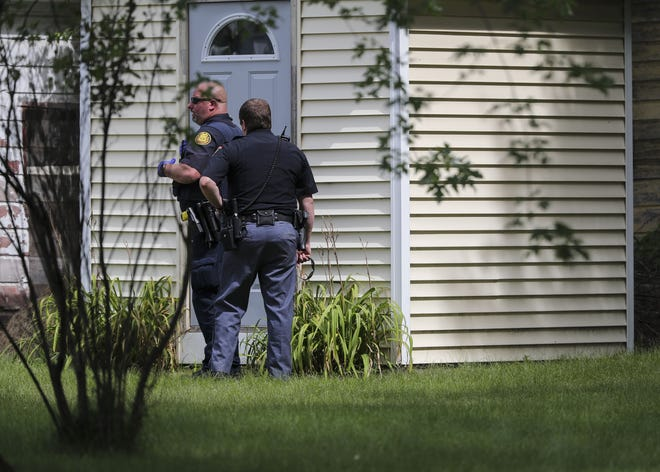 Police stand watch Tuesday outside a home in the 2500 block of Water Street, Stevens Point, after they say a man barricaded himself on the roof. Police say the man led on a chase, crashed into a house on Prairie Street and ran from the scene.
