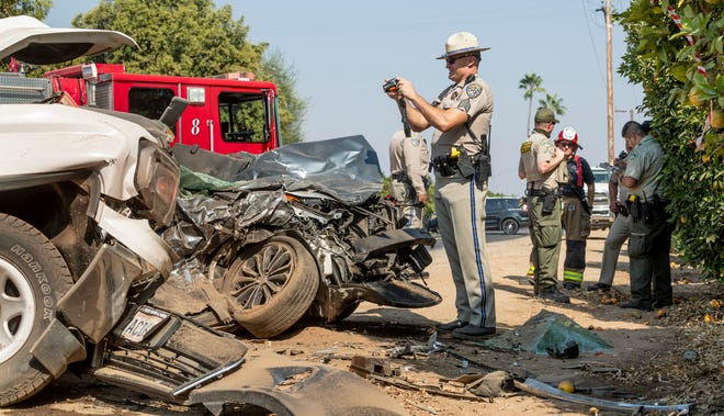 CHP Sgt. Michael Donnelly photographs the scene as others investigate a fatal collision on Monday, August 30, 2021. on Avenue 336 just west of Road 162. An adult male was killed when the Toyota he was driving left the roadway, overcorrected, entered the east bound lane and collided with the GMC truck. He died at the scene from injuries of the impact. The truck driver refused medical attention and was transported from the scene by family.