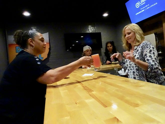 Front-of-house manager Staci Berry serves Beverly Thomas a drink at Urban Comforts Eatery. The downtown Zanesville restaurant is one of many local businesses struggling in a labor shortage.