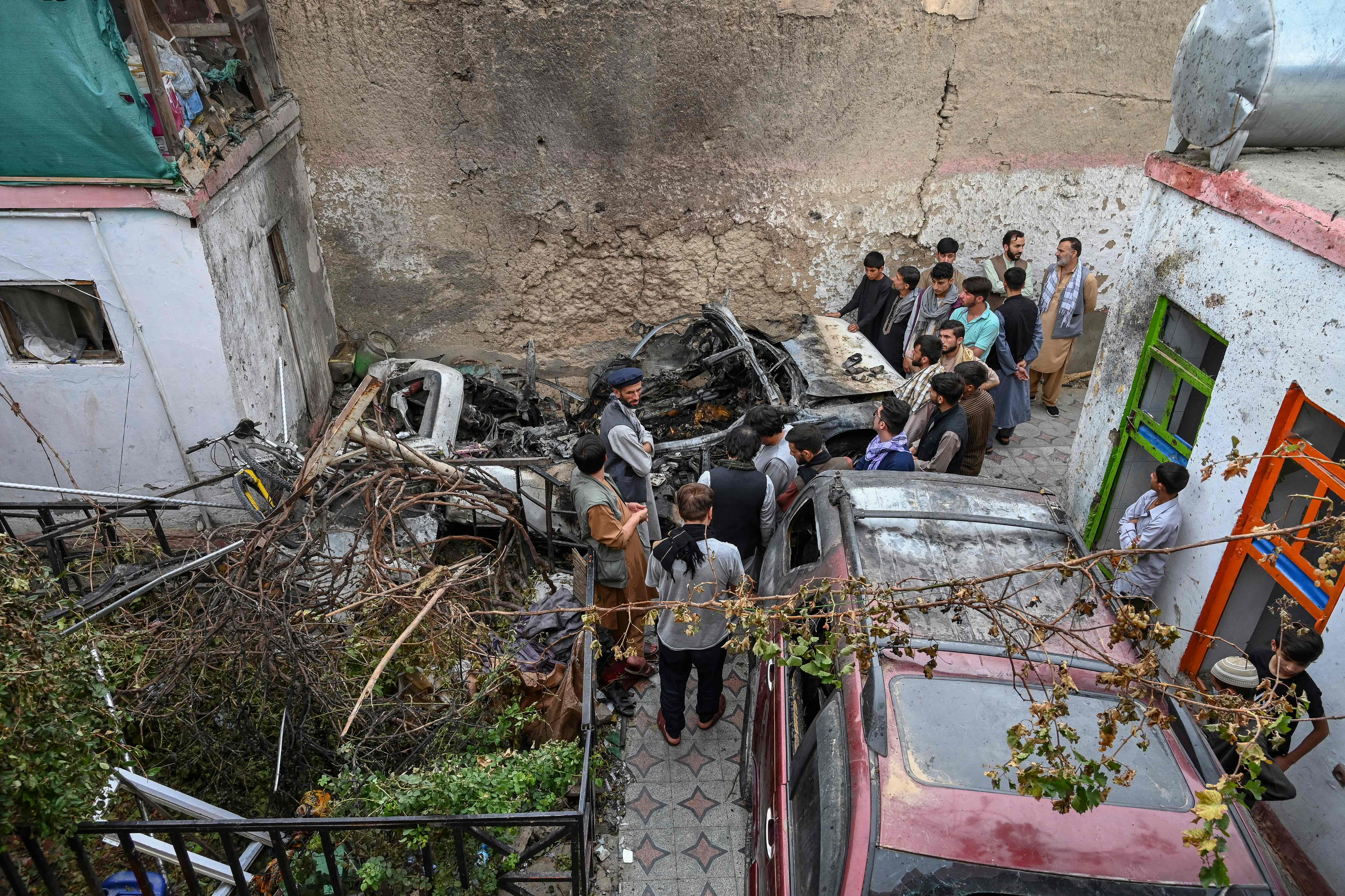 Afghan residents and family members of the victims gather next to a damaged vehicle inside a house, day after a US drone airstrike in Kabul on August 30, 2021. (Photo by WAKIL KOHSAR / AFP) (Photo by WAKIL KOHSAR/AFP via Getty Images) ORG XMIT: 5268 ORIG FILE ID: AFP_9LW4JY.jpg