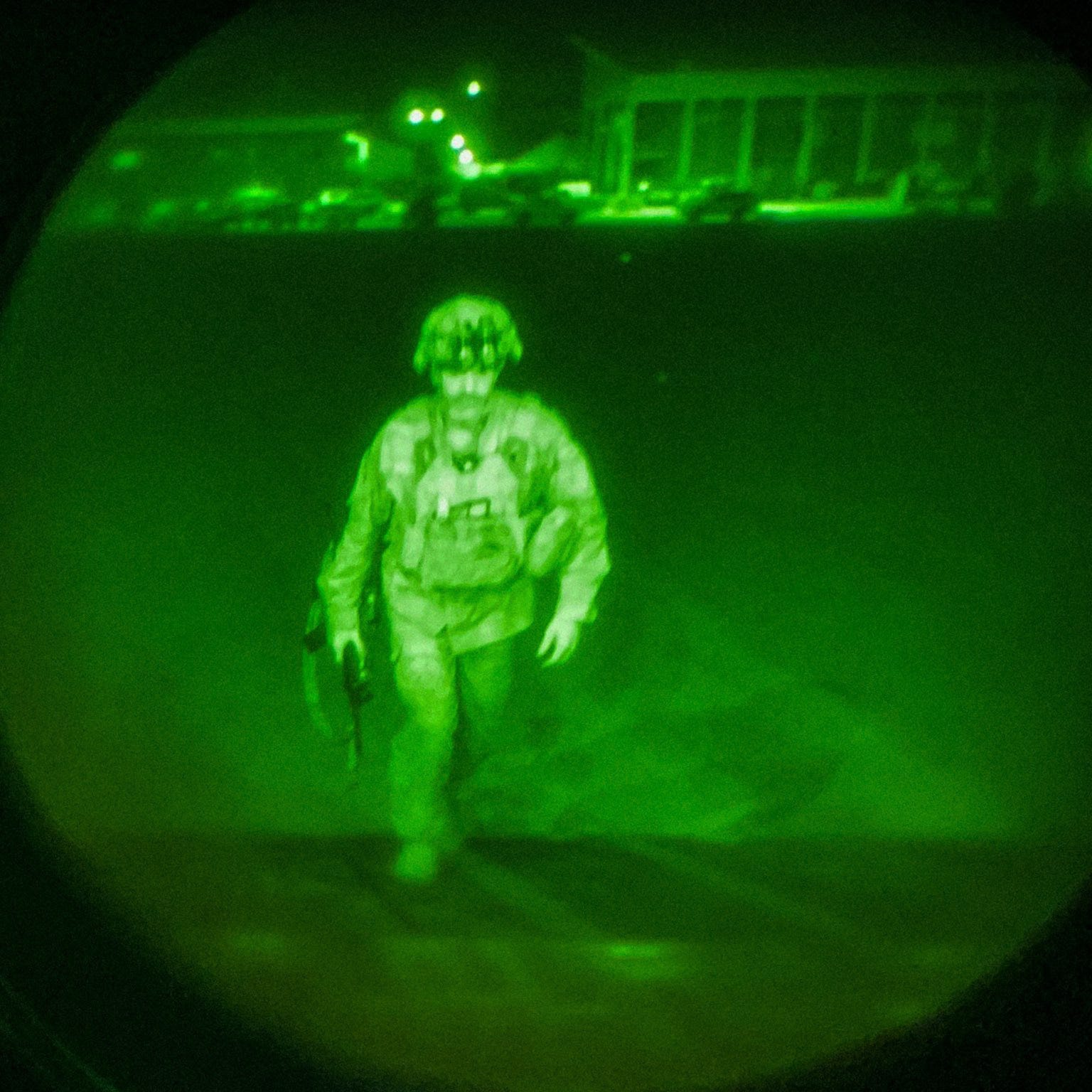 A soldier is seen walking through a night vision lens.