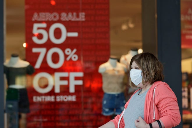 A shopper walks past a store in Great Lakes Mall in Mentor, Ohio, in this file photo.  Shoppers are contending with the ongoing coronavirus pandemic, inflation and supply chain disruptions.