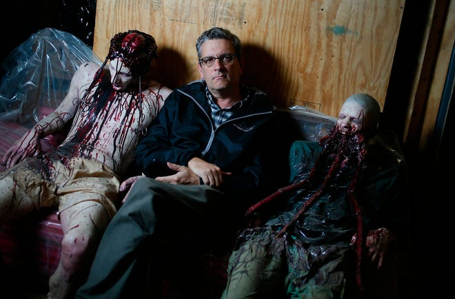Craig Webb poses for a portrait with monsters while on an assignment at the Ghoul Brothers Haunted House in Akron.  (Leah Klafczynski/Beacon Journal file)