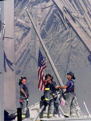 Firefighters raise a flag late in the afternoon on Tuesday, Sept. 11,  2001, in the wreckage of the World Trade Center towers in New York. In the most devastating terrorist onslaught ever waged against the United States, knife-wielding hijackers crashed two airliners into the World Trade Center, toppling its twin 110-story towers.