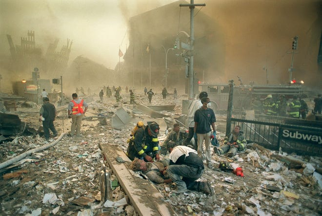 Firefighters and rescue personnel tend to the injured amidst the ruins of the World Trade Center shortly after their collapse on Sept. 11, 2001. (Justin Lane/The New York Times)