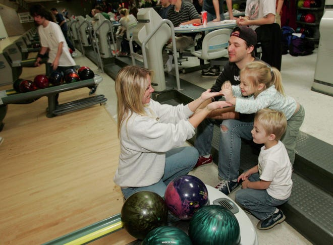 Marijean Benedik, left, of Ravenna, claps the hands of her daughter Skylar, 3, after knocking down some pins as her husband John Benedik and their son Johnny, 4, enjoy an evening of family bowling at the Sto-Kent Family Entertainment bowling alley Nov. 16, 2007, in Stow.