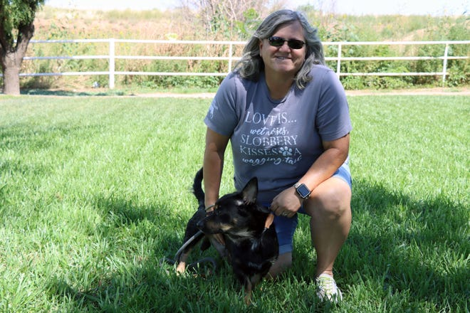 Cheryl Goswick, a volunteer with Gracie's Project, hangs out with Biggy Smalls, a rescue dog, at Hope Veterinary Clinic.