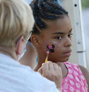 Arianna English, 9, right, sits patiently as Ellen Stevens, left, puts the finishing touches on face art Saturday, Aug. 28, 2021, at a back-to-school bash at The Alliance Church of the Nazerene on South Arch Avenue.
