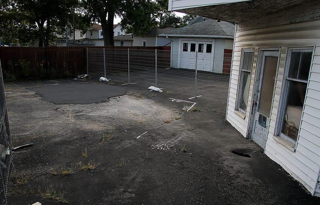 After fixing the sinkhole on E. Main Street, which can be seen with the newer asphalt, another one has shown up this time much closer to the structure on the property seen here on Wednesday, Sept. 1, 2021. TOM E. PUSKAR/TIMES-GAZETTE.COM